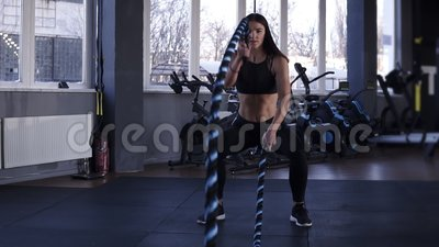 Woman training in gym with battle ropes. Powerful attractive caucasian woman do battle workout with ropes at the gym in. Slow motion. Front view stock video
