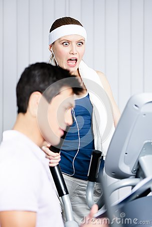 Woman training on gym equipment in gym with coach