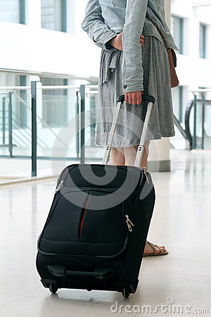 Woman with travel suitcase at international airport