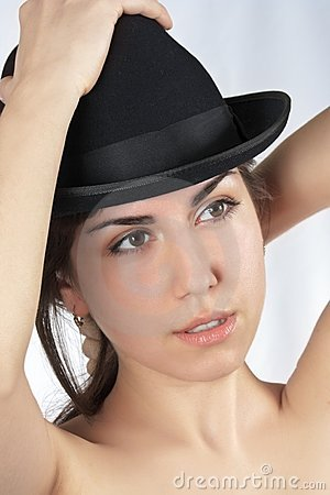 Woman tries on a black hat