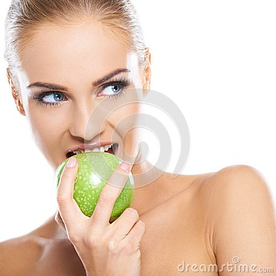 Woman tries to bite a fresh green apple