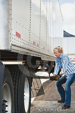 Woman Truck Driver Raising Trailer legs