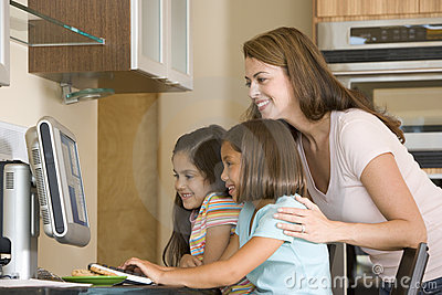 Woman and two girls in kitchen with computer