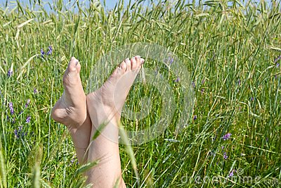 Woman two legs in green grass field under blue sky