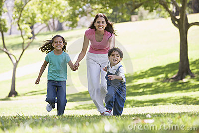 Woman with two young children running smiling