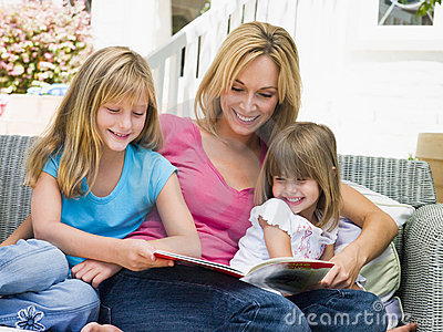 Woman and two young girls sitting on patio reading