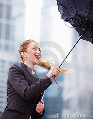 Woman with umbrella fighting with strong wind