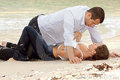 Woman is unbuttoning shirt on man as they lay on t