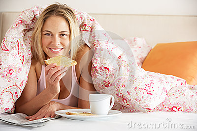 Woman Under Duvet Eating Breakfast
