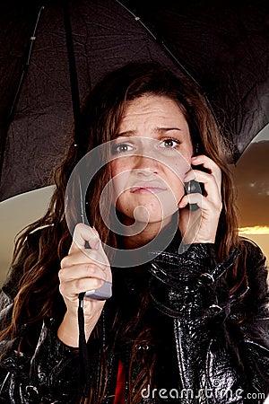Woman under umbrella on phone