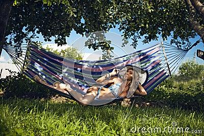 Woman in underwear has a rest in a hammock