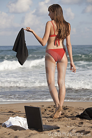 Woman undresses on the beach