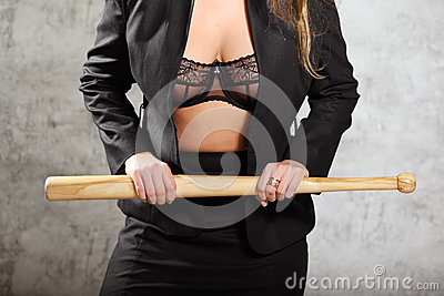 Woman in unfastened suit in bra hold bat