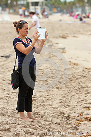 Woman Uses Tablet Computer To Capture Family Images On Beach Editorial Stock Photo