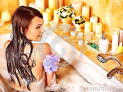 Woman using bath sponge in bathtub.