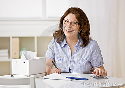 Woman using calculator to pay monthly bills