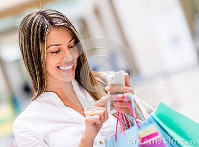 Woman using cell phone while shopping