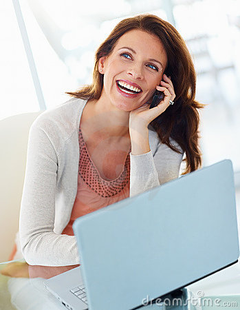 Woman using cellphone with laptop in front