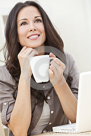 Woman Using a Computer and Drinking Tea or Coffee