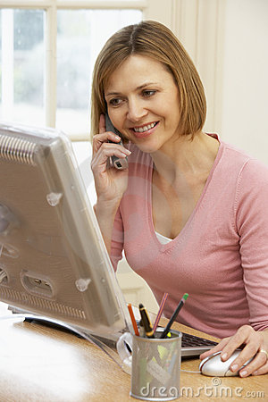 Woman Using Computer And Talking On Phone