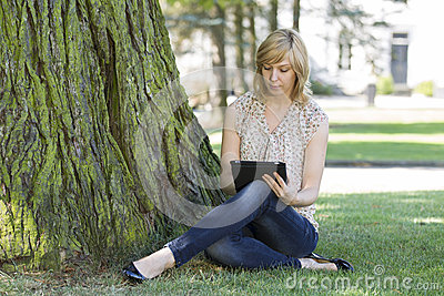 Woman using digital tablet by tree on lawn