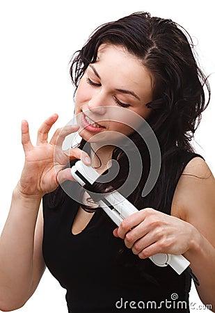 Woman is using hair straightener
