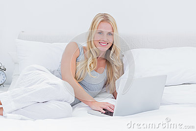 Woman using her laptop laid on her bed