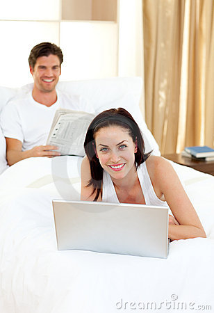 Woman using her laptop and man reading newspaper
