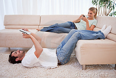 Woman using her phone while her boyfriend is using a tablet