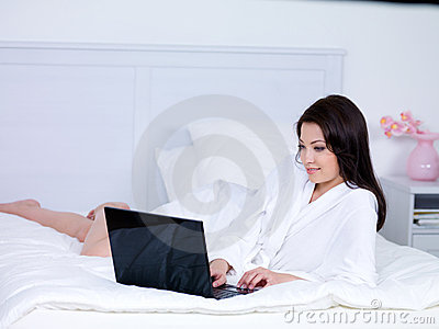 Woman using laptop on a bed