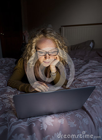 Woman using laptop in bed at night 002