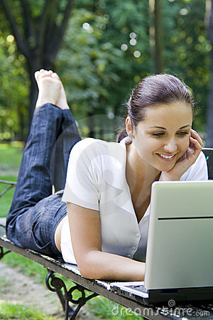 Woman using laptop on bench outdoors