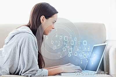 Woman using laptop with binary codes floating over
