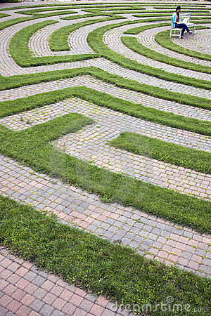Woman Using Laptop in a Cobblestone Maze