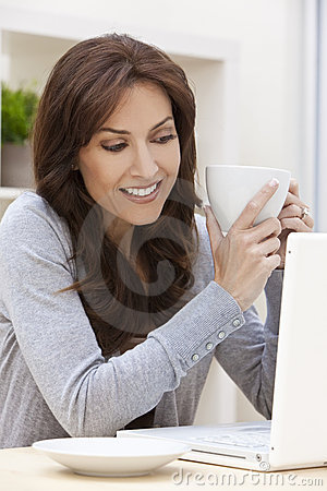 Woman Using Laptop Computer Drinking Tea or Coffee