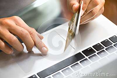 Woman using laptop and credit card.close-up hands