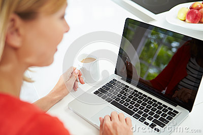 Woman Using Laptop At Home In Kitchen