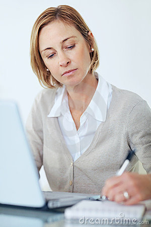 Woman using a laptop making a note in notepad