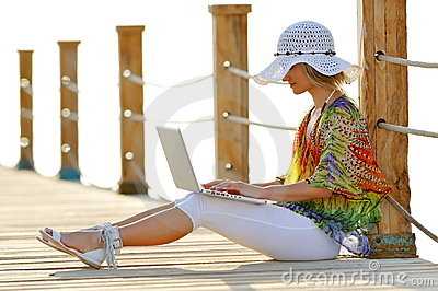 Woman using laptop outdoor in summer