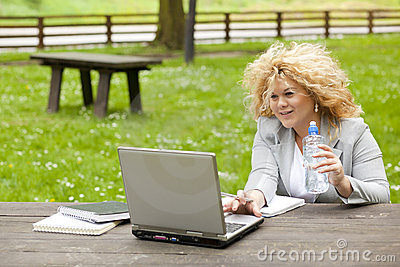 Woman using laptop in park and drink water Stock Photo