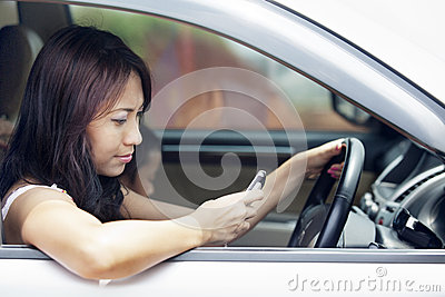 Woman using mobile phone while driving