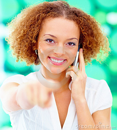 Woman using a mobile phone pointing at you