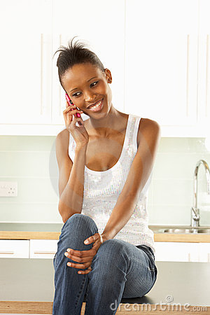 Woman Using Mobile Phone Sitting In Kitchen