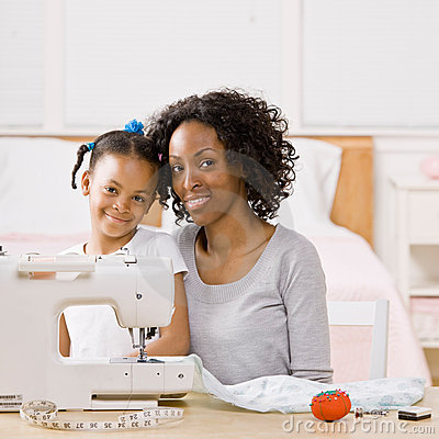 Woman using sewing machine with daughter