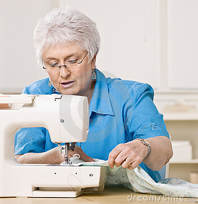 Woman using sewing machine at home