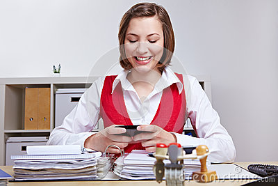 Woman using smartphone at desk in office