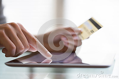 Woman using tablet pc and credit card