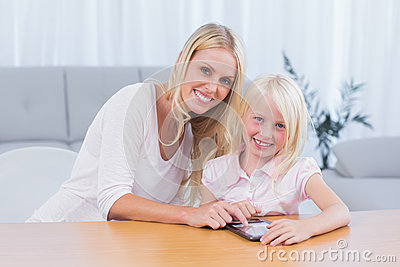 Woman using tablet pc with her daughter
