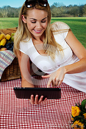 Woman using a tablet on a picnic