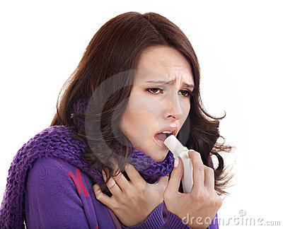 Woman using throat spray.